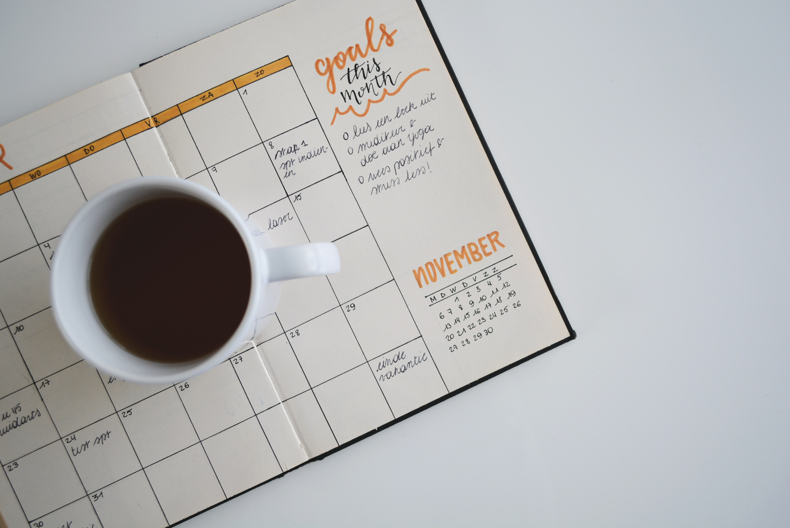 personal calendar open, there is a coffee mug over it