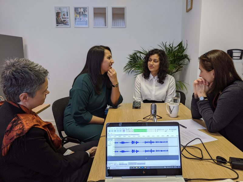Sitting around a desk: Nicola, Kiran, Amna and Vicky. There is a computer on the foreground and a microphone on the desk