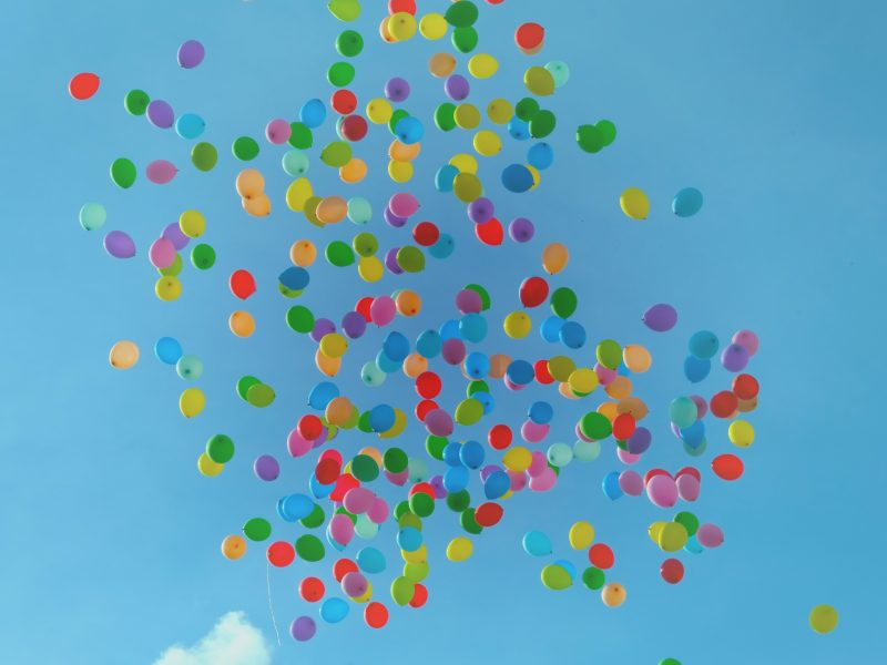 coloured balloons flying over a blue sky