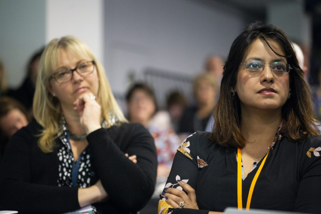 Two women sat next to each other listening to a speaker