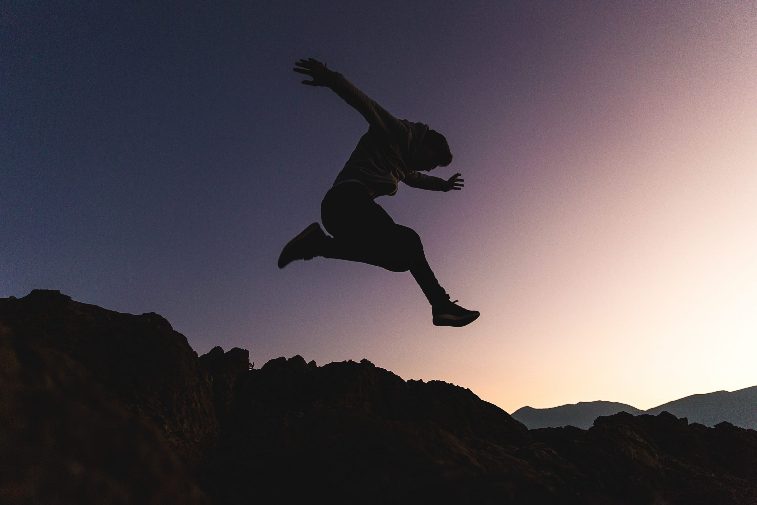 person jumping, sunset background