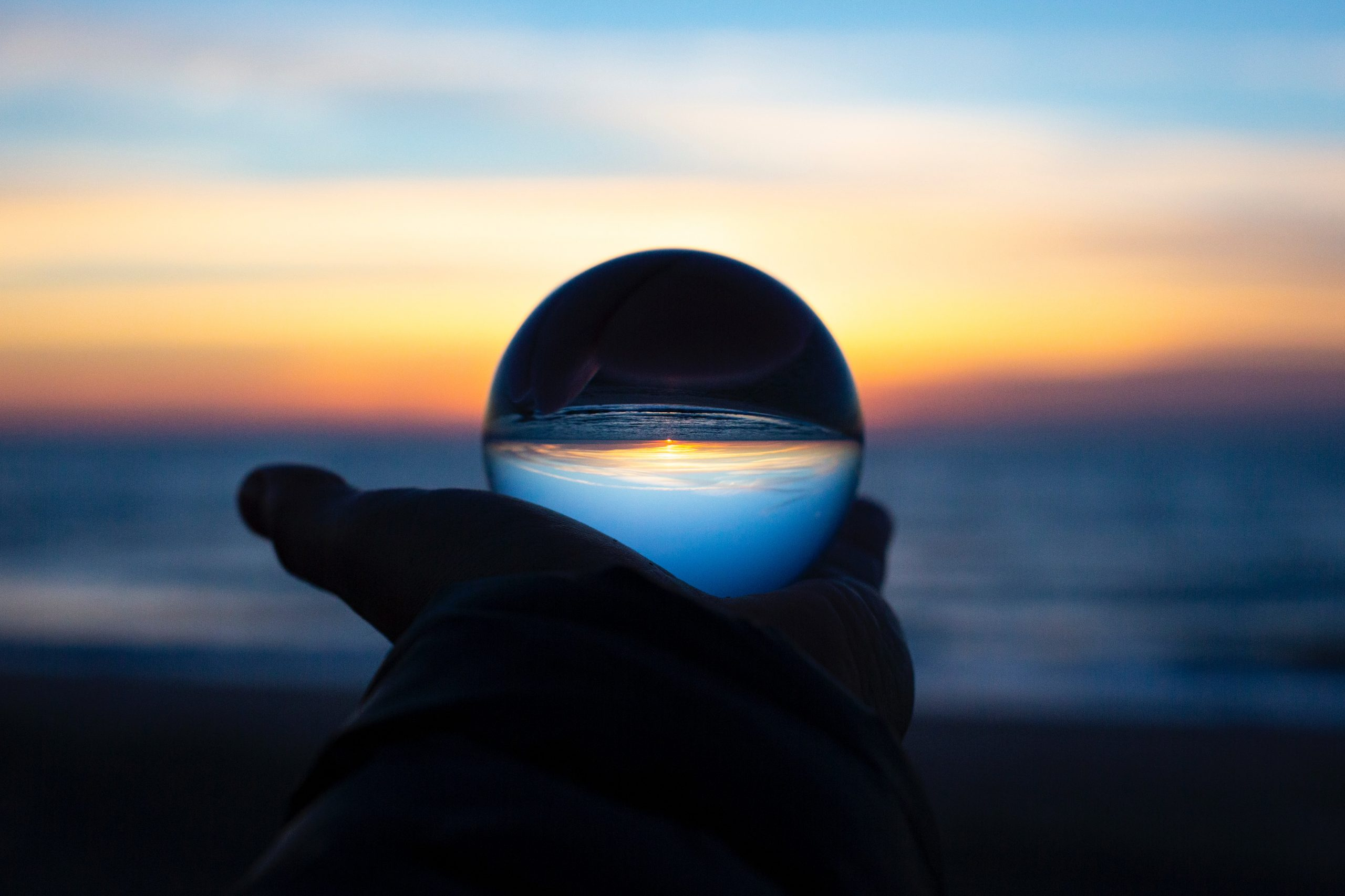 hand holding a clear glass ball in front of the sea. The sea and the sky are reflected on the ball, appearing upside down