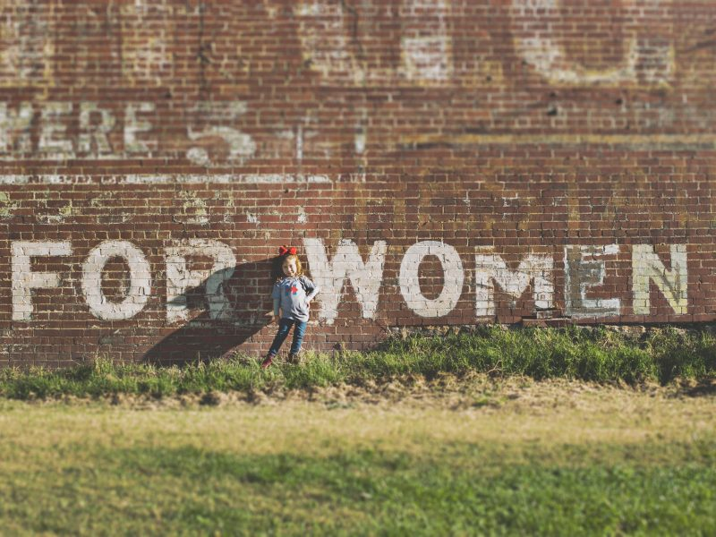 girl standing in front of brick wall with the words For Women painted over it