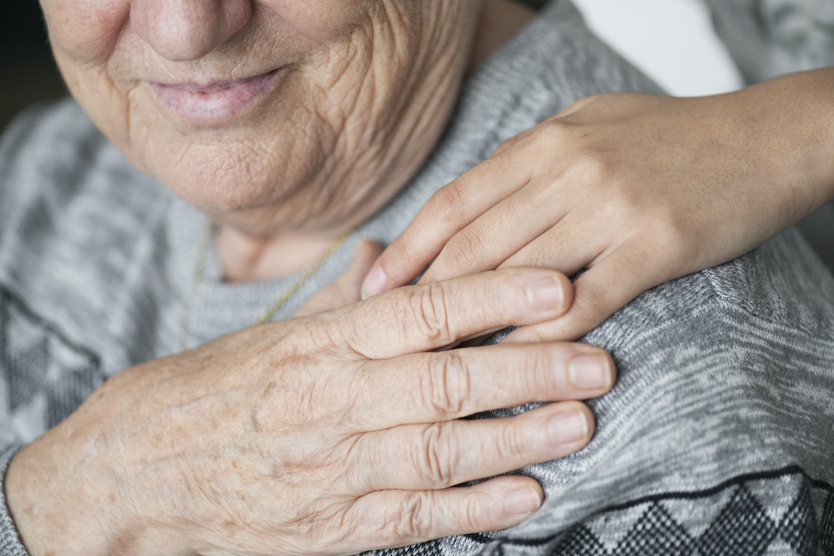 close up of a shoulder and face of an elderly person, their hand in holding someone else's hand which is over their shoulder