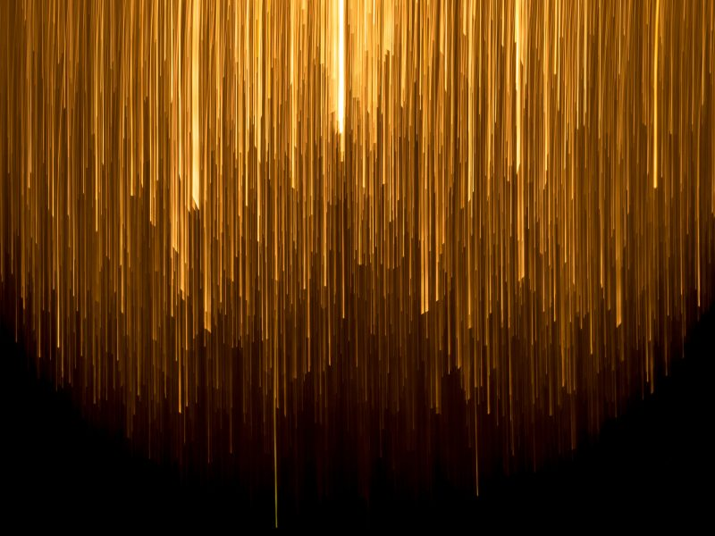 abstract image, looks like golden ribbons placed vertically in different lengths against a dark background