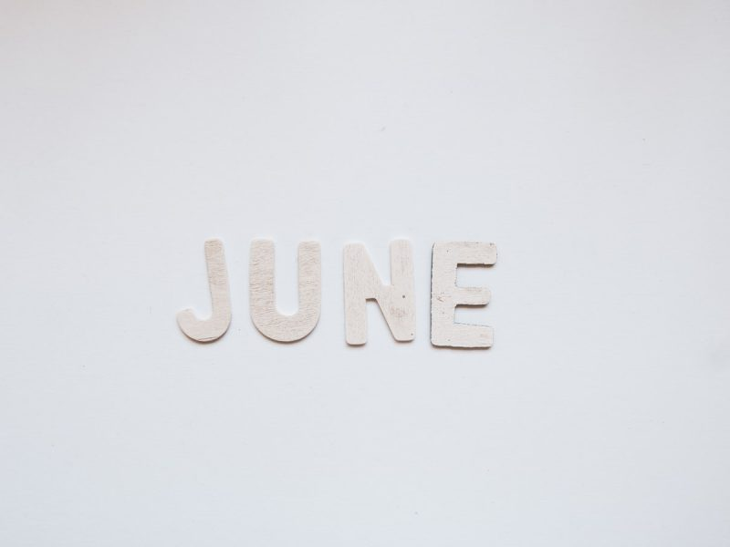 'June' written using paper cut letters, over a white background