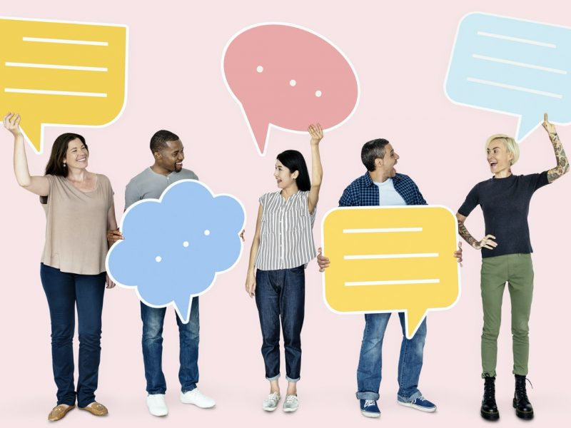 5 people standing up holding conversation bubbles