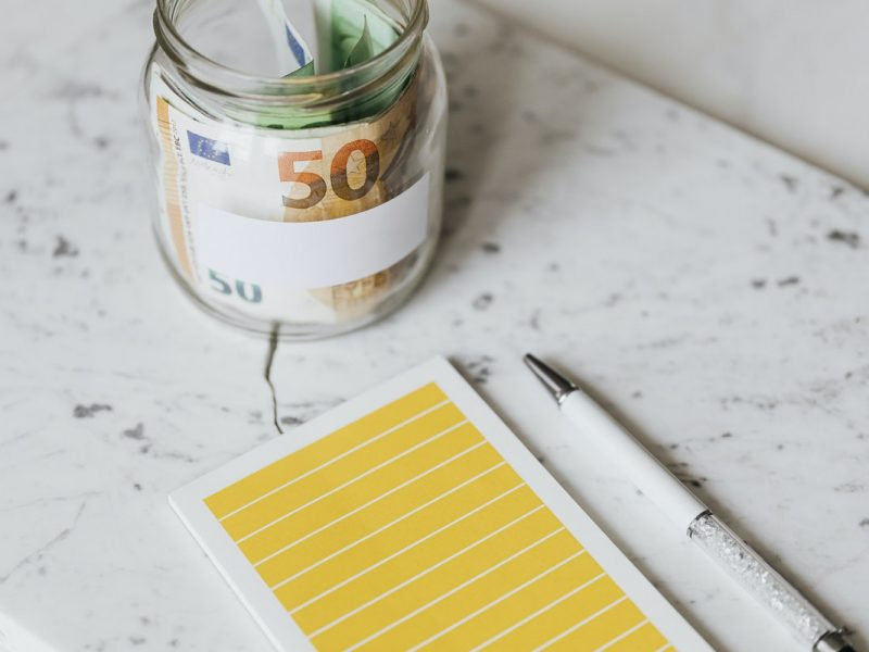 a glass jar with cash in it, near a blank notepad and a pen