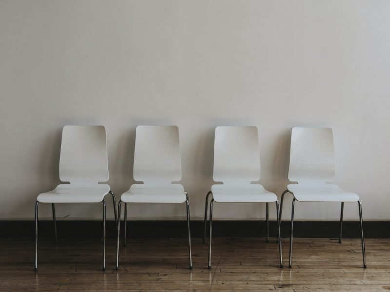 four white chairs against a white wall