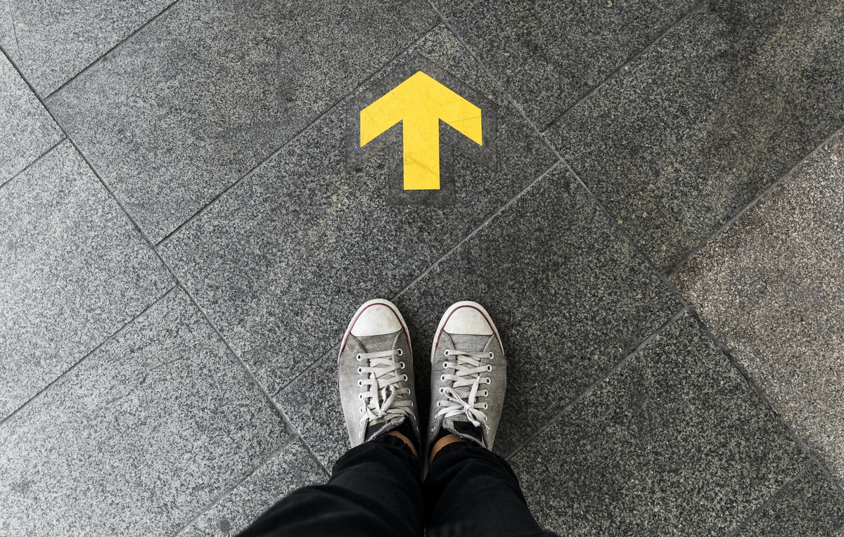 a person standing near a yellow arrow pointing forward, painted on the pavement