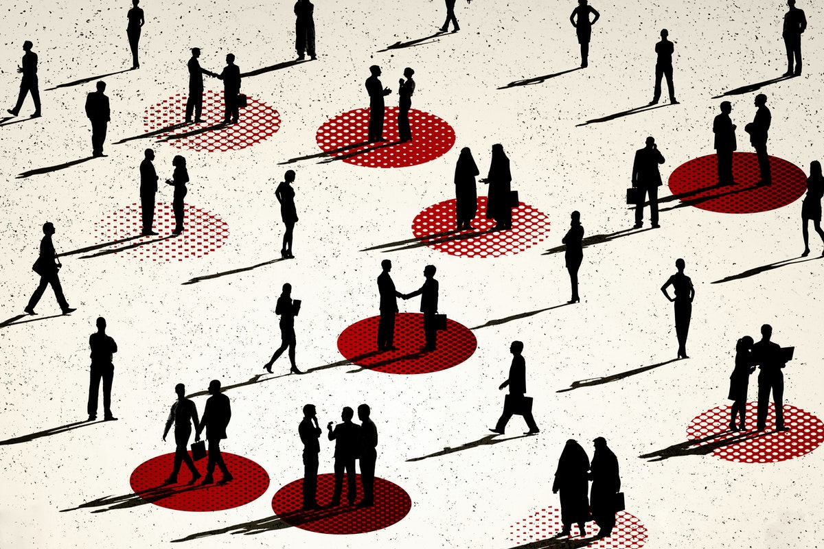 lots of people seen from afar, we can only see their profiles in black. some of them are talking to each other, some are walking. there is some distance between everyone, and some small groups stand over red circles painted on the floor.