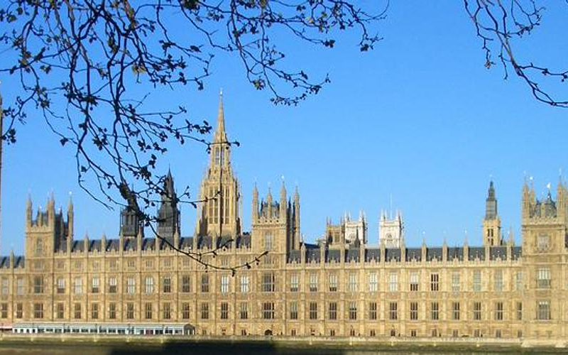 A photograph on the Houses of Parliament in front of a clear blue sky.