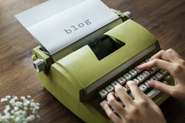photo of a person using a green typewriter, a paper still inside says 'blog'